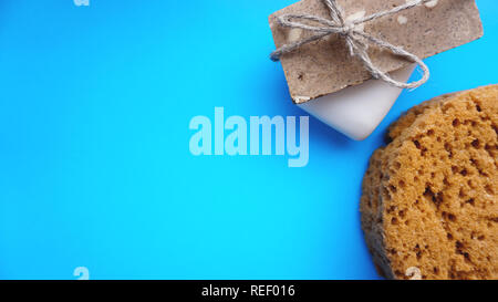 Handmade soap wrapped with twine on a blue clean background - Stock Photo