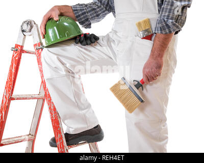 House painter worker on the ladder with white work overalls, keeps the roller for painting in his hand. Equipped with shoes, helmet and protective glo - Stock Photo