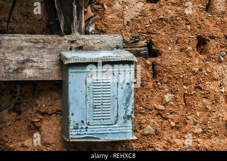 Old weathered grunge obsolete metal tin post letter box on adobe clay wall of abandoned rural country house closeup - Stock Photo