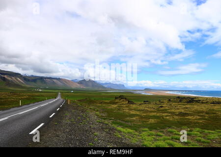Street in Iceland landscape with mountains, beach and lava - Stock Photo