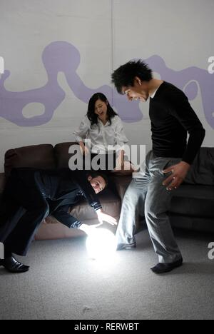 Young business team around a brightly glowing globe - Stock Photo