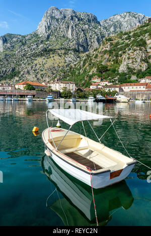 Boats in the Bay of Kotor with mountains rising above the city in Kotor, Montenegro - Stock Photo