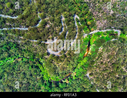 Serpentine twisted Galston road on steep hill side down to Berowra creek in a valley through gum-tree woods with intense traffic seen from above top d - Stock Photo