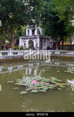Looking at the back of the entrance gate at the Temple of Literature in Hanoi, Vietnam. Lily pond in the foreground. - Stock Photo