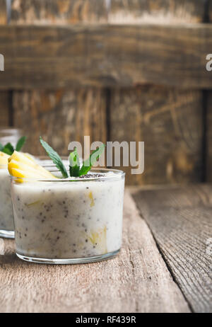 Mango banana smoothie in glass, healthy dessert with natural greek yoghurt and chia seeds, vegetarian breakfast with honey on wooden rural table, clos - Stock Photo