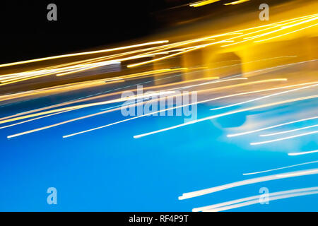 Bright direct white and yellow light strips on black-yellow-blue background.  - Stock Photo