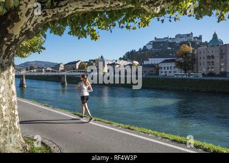 Salzburg, Joggerin an der Salzach, im Hintergrund die Festung Hohensalzburg - Salzburg, Jogging along the Banks of River Salzach, Hohensalzburg Castle - Stock Photo