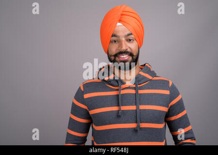 Young handsome Indian Sikh man wearing orange turban - Stock Photo