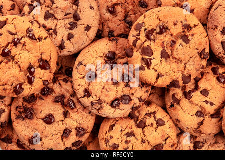 Many freshly baked chocolate chip cookies, shot from the top on white, an abstract sweet biscuits texture - Stock Photo