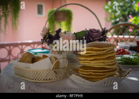 Fresh ordinary pancakes served for breakfast. Breakfast table with flowers and other dishes. - Stock Photo