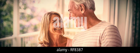 Happy senior couple interacting with each other in balcony - Stock Photo