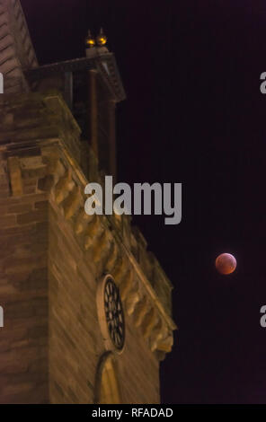 21st January 2019 supermoon. The blood moon of the total lunar eclipse illuminates the medieval clock tower of St John's Kirk in Perth city centre. - Stock Photo