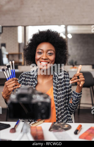 Cute african american woman with curly hair making photo for fashion magazine - Stock Photo