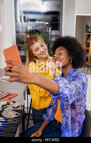 Amazing african american model with coral lipstick making selfie - Stock Photo
