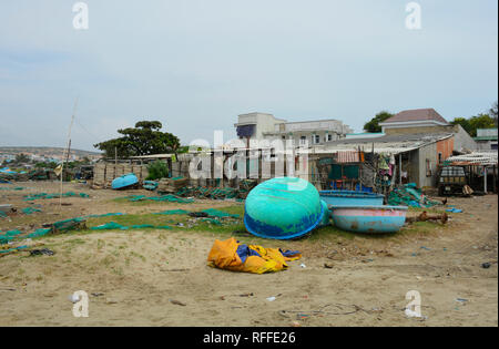 Mui Ne, Vietnam - December 27 2017. Houses and traditional round fishing boats at Mui Ne Fishing Village. Despite being a major tourist attraction in  - Stock Photo