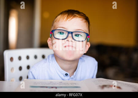 Cute toddler boy with down syndrome with big glasses reading intesting book. - Stock Photo