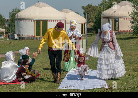 High stepping 'Tusau Kesu' ceremony (cutting the rope) enthusiastic child with family in festive attire, Almaty, Kazakhstan - Stock Photo