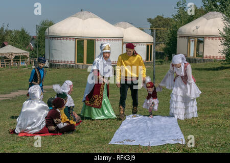 'Tusau Kesu' ceremony (cutting the rope) the first step with family in festive attire, Almaty, Kazakhstan. - Stock Photo