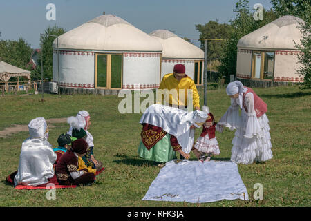 'Tusau Kesu' (cutting the rope) first steps ceremony with family in festive attire, Almaty, Kazakhstan - Stock Photo