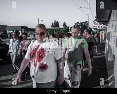 Men dressed as zombies parade on a street during a June 2010 zombie walk flash mob in Michigan - Stock Photo