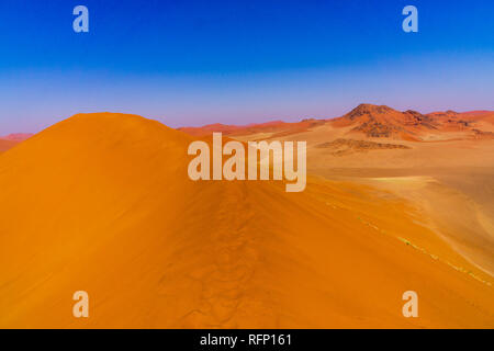 SOUSSUSVLEI, NAMIBIA - JUNE 20, 2016: People watching sunrise form the Dune 45 in the Sossusvlei area of the Namib Desert in Namibia. - Stock Photo