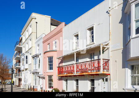 Georgian houses in Grand Parade, Old Portsmouth, Hampshire, UK including terraced houses with pink bow-fronted window and red wrought iron balcony - Stock Photo