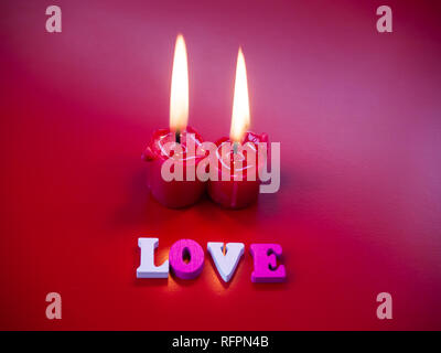 Concept of love Red candles lit and the word love with a red background - Stock Photo