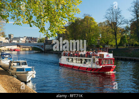 Pleasure boats moored along the River Ouse and a York Boat full with tourists on a sightseeing river cruise, York, Yorkshire, England, United Kingdom - Stock Photo