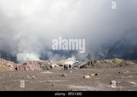Three people walk back to the helicopter that has landed them in the crater of the volcano on Whakaari, White Island, New Zealand. - Stock Photo