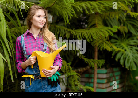 gorgeous beautiful girl in uniform holding a water can - Stock Photo