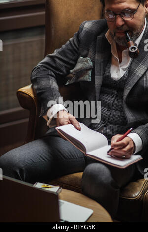 Fifty years old businessman making notes on the paper, smoking a tobacco pipe - Stock Photo