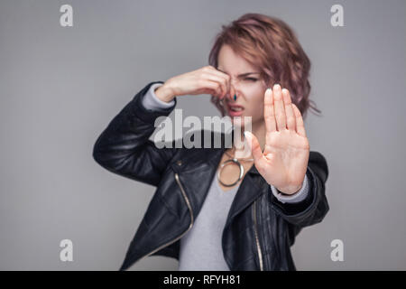 Stop, bad smell. Portrait ignoring of beautiful girl with short hairstyle and makeup in casual style black leather jacket standing pinching her nose.  - Stock Photo