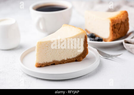 Cheesecake New York with cup of coffee on white table. Closeup view. Coffee break with slice of cake and black coffee - Stock Photo