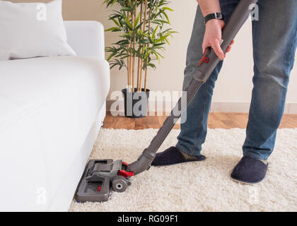 Using vacuum cleaner and cleaning the carpet - Stock Photo