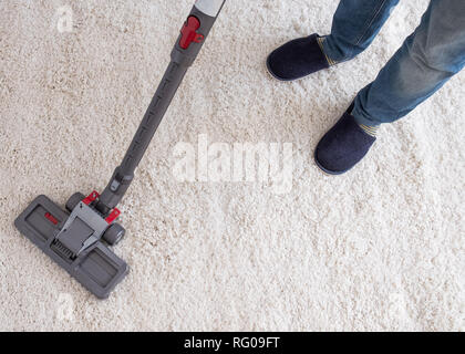 Vacuuming the living room carpet at home - Stock Photo