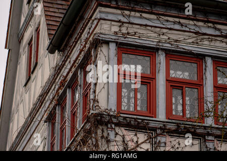 Half-timbered house with red windows ingrown with wild wine - Stock Photo
