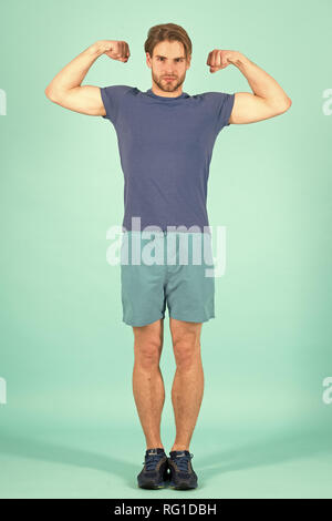 Athlete flex muscles with biceps. Fashion sportsman in blue sport uniform. Bearded man with stylish hair. Power and fitness concept. - Stock Photo