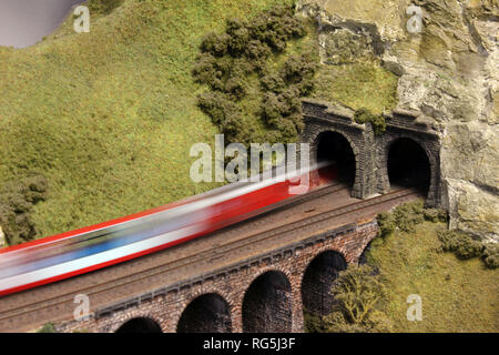 Electric Model Train on miniature train track going through mountain tunnel - Stock Photo