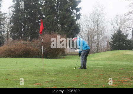 Man putting a golf ball on a golf course in winter, Germany - Stock Photo