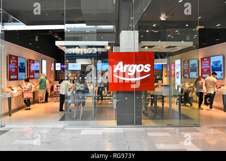 Shoppers behind glass building shop front window at Argos catalogue shopping store in Westfield mall in Stratford City Newham East London England UK - Stock Photo