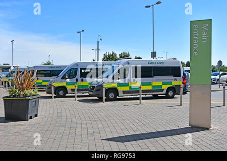 Row of G4S patient delivery healthcare ambulance parked outside the main entrance sign to NHS Queens Hospital  Romford Havering East London England UK - Stock Photo