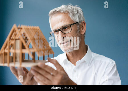 Successful architect looking at model of a house - Stock Photo