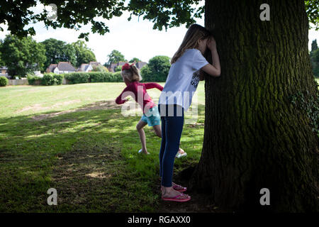 two young girls playing hide and seek in a park in Summer - Stock Photo