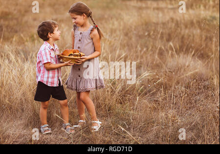 Little boy with girl drink hold a loaves of bread in a village at sunset. Brother and sister walking in the field. - Stock Photo