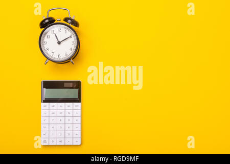 dial of the alarm clock and stylish modern calculator lie isolated on the side of the yellow table. Place for writing. Can be used as a business backg - Stock Photo