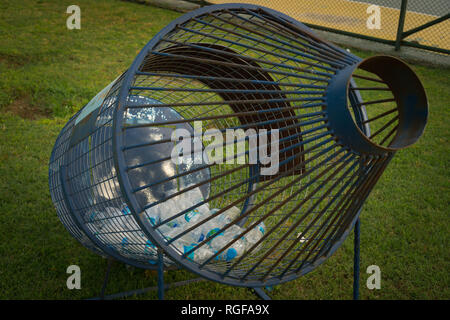 Empty plastic bottles gathered for recycling in steel cage in shape of bottle. - Stock Photo