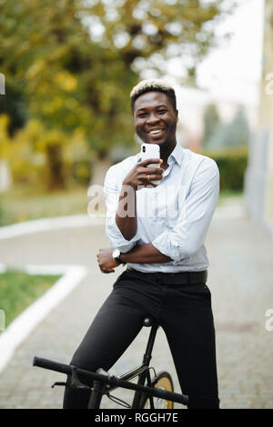 Portrait of a young African man smiling and reading a text message on his cellphone while standing with his bicycle on a city street - Stock Photo