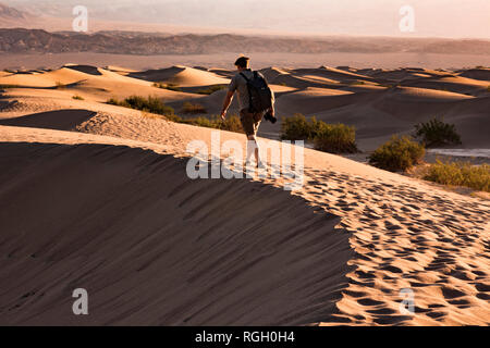 USA, Californien, Death Valley, Death Valley National Park, Mesquite Flat Sand Dunes, man walking on dune - Stock Photo