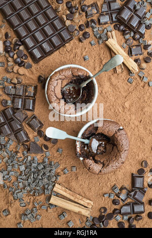 Homemade Chocolate Fondant Pudding surrounded by cocoa powder and dark chocolate chunks - Stock Photo