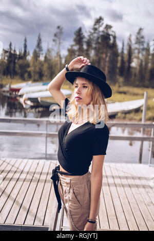 Sweden, Lapland, portrait of fashionable blond woman wearing black hat standing on jetty - Stock Photo